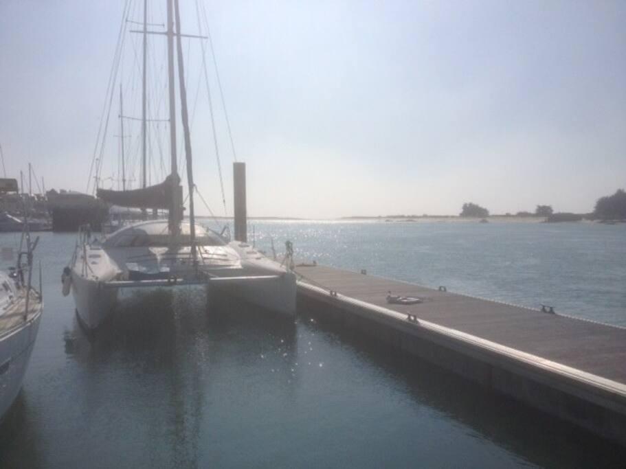 Le catamaran au ponton, avec, au fond, la Barre d'Etel, ouverte sur l'Océan Atlantique