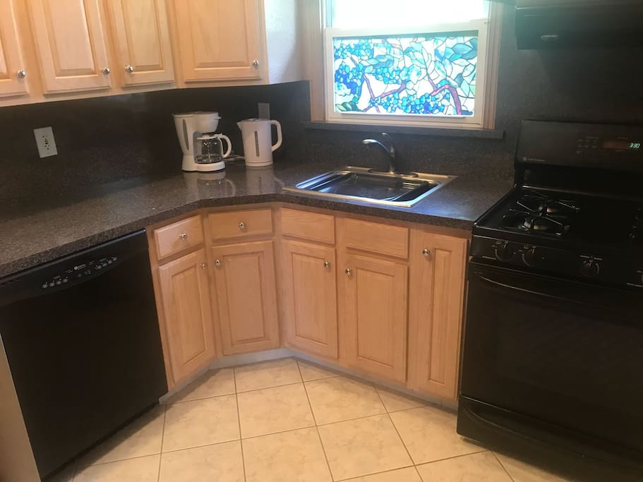Kitchen area with coffee maker and hot water kettle shown. Also has microwave, toaster, stove. with oven.
