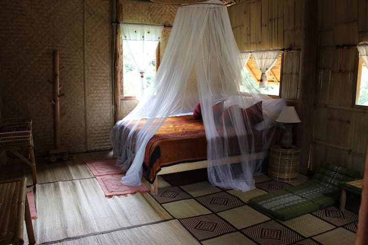 Private bedroom with bed and mosquito net.