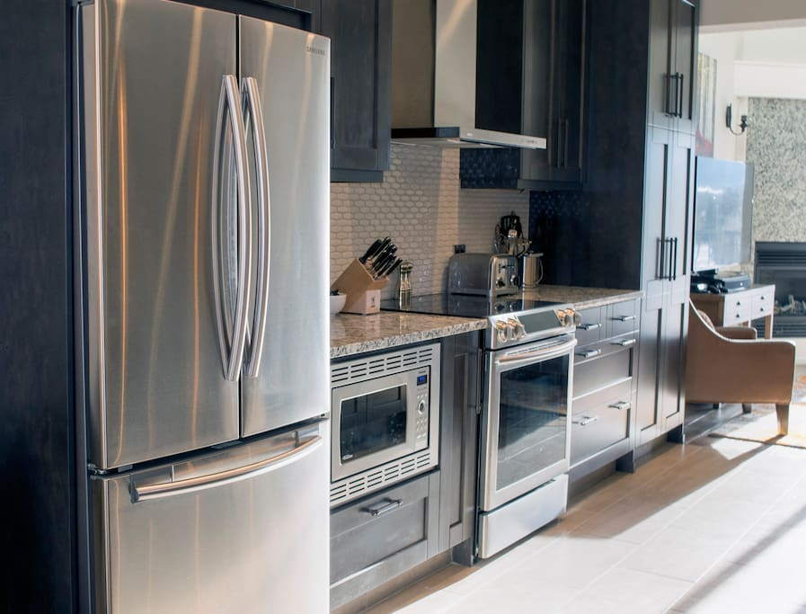 Gourmet kitchen with stone counters and new appliances makes cooking a breeze.