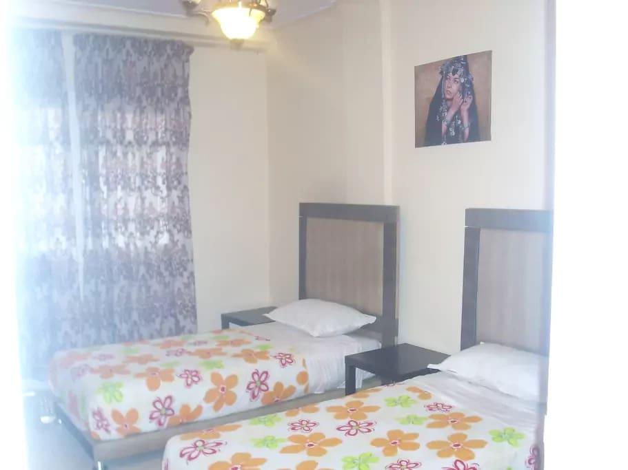 chambre avec 2 lits simples et un fauteuil.