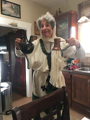 "Your host, Elaine, wearing traditional Ethiopian garb while performing ""Romancing the Bean"" coffee-tasting experience."