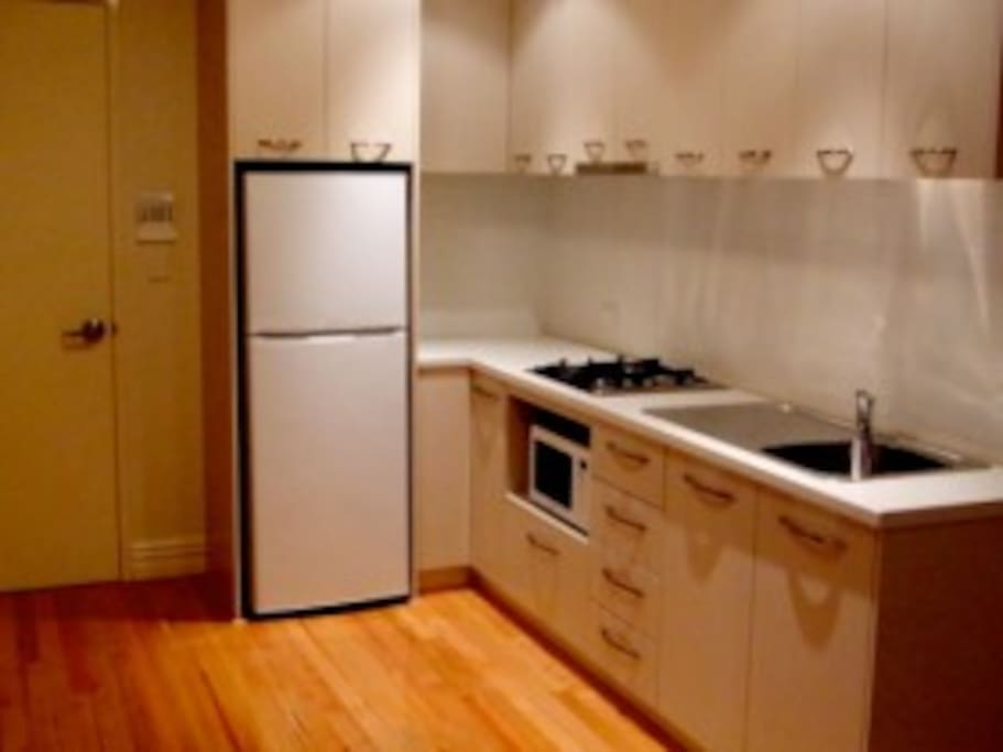 Kitchen has full size refrigerator microwave oven and 4 burner cooktop.