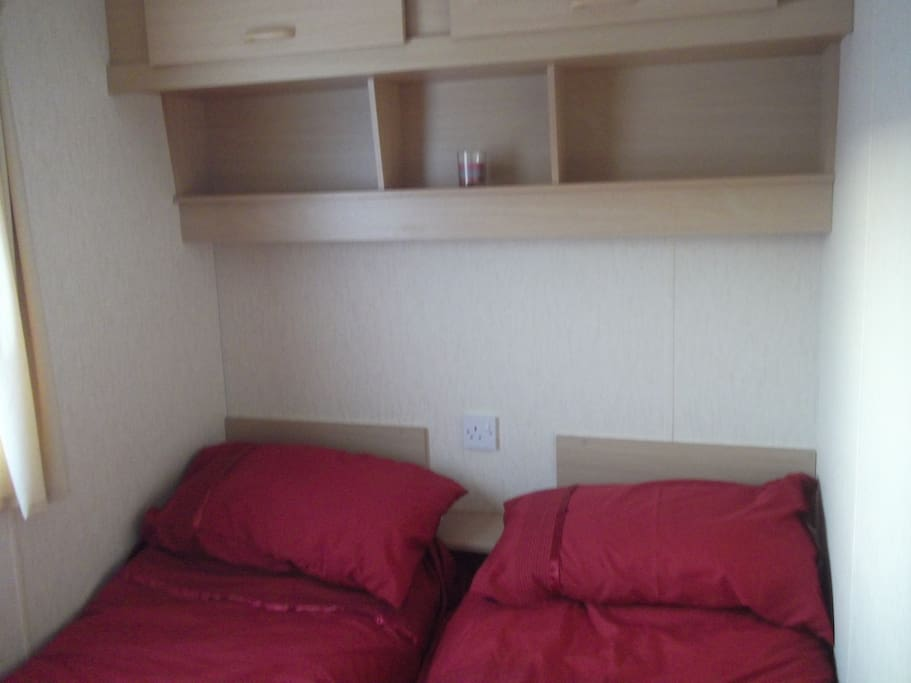 This is the twin bedroom, with two single beds, one wardrobe and overhead cupboards