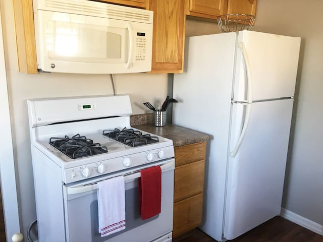 Kitchen with gas range/oven, built in microwave, refrigerator.