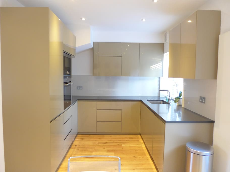Bespoke fitted kitchen with induction hob, oven, microwave, dishwasher and combined washer/dryer