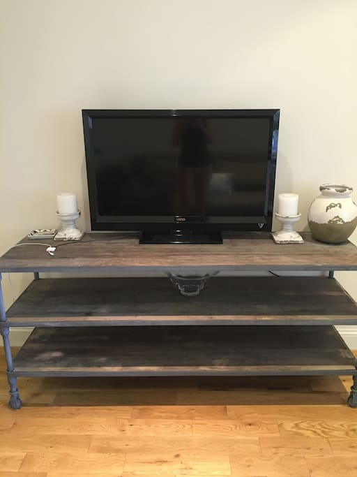 Restoration Hardware furniture with large TV and connections for watching apps.