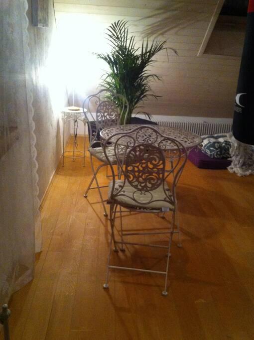 Weisser Tisch mit 2 Stühlen vor Fenster