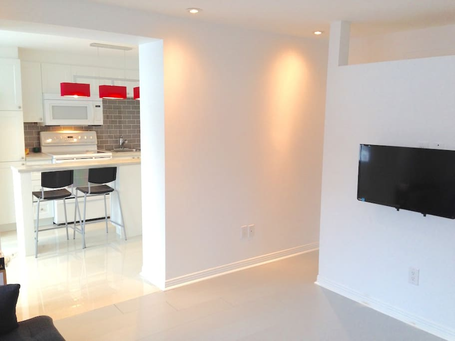 Adjacent to the kitchen is the living room, equipped with a flat screen HD TV.