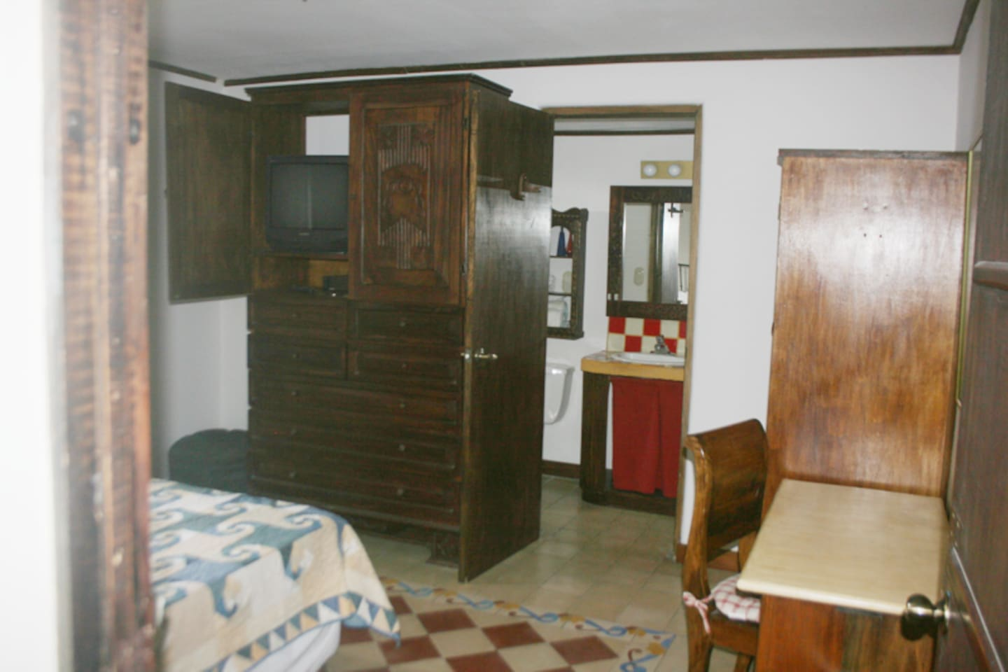 Same room, different angle and somewhat smaller bed. There's a small desk, a chair, and beside that there's a closet with hangers. Under the TV there are drawers for you to put your things. The open door you see is the door to the private bathroom.