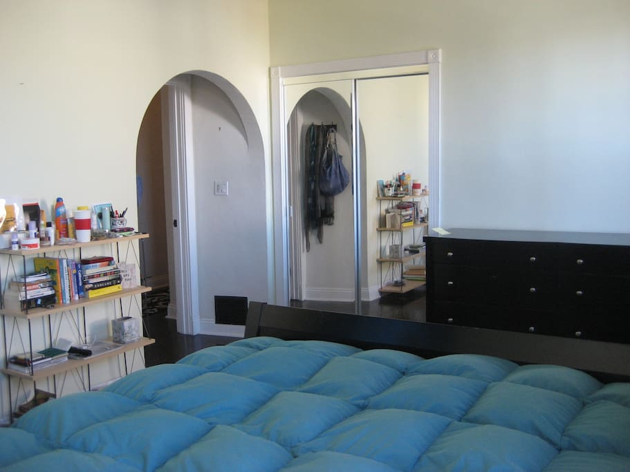 Queen size bed in a well-lit room with a view of the Hollywood sign from your pillow!