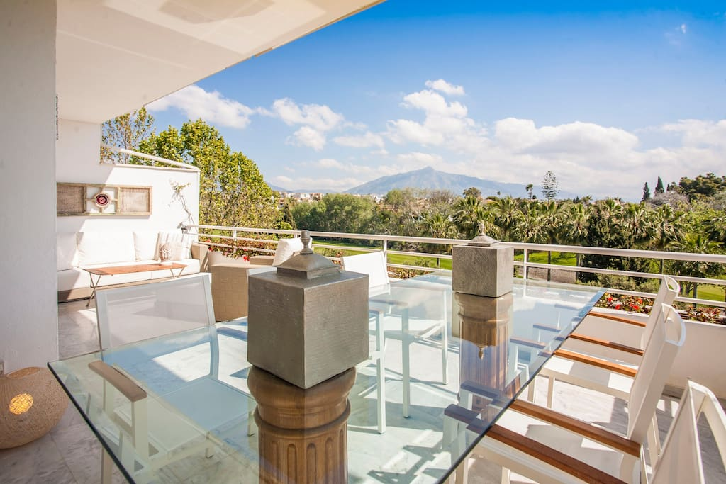 Ample terrace with outdoor dining and lounge areas overlooking Guadalmina south golf club