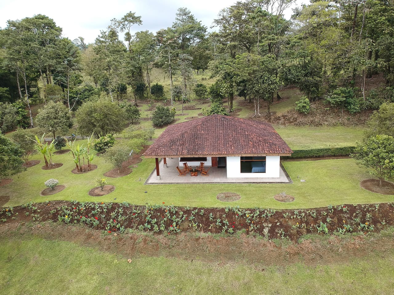 A home in the middle of green beautiful trees and well take care gardens. I welcome you to enjoy the beauty of a home away from the city but yet very close to Tenorio Volcano National Park.  Here you can find a panoramic view of the house.
