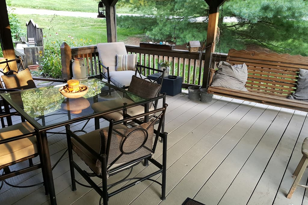Table for 4 under covered porch with ceiling fan right next to water garden.