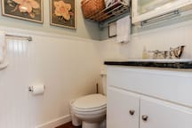 Three piece bathroom has a shower with a bench. Blower dryer, shampoos, and other essentials are provided.