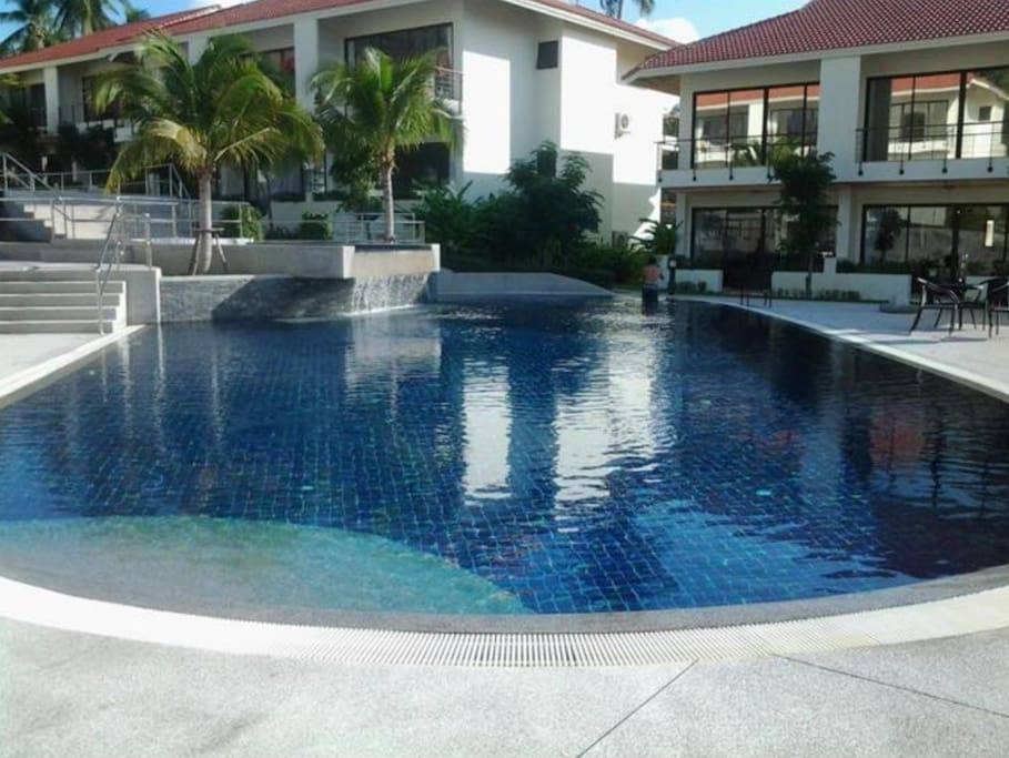 Huge swimming pool with waterfall also separate child friendly pool