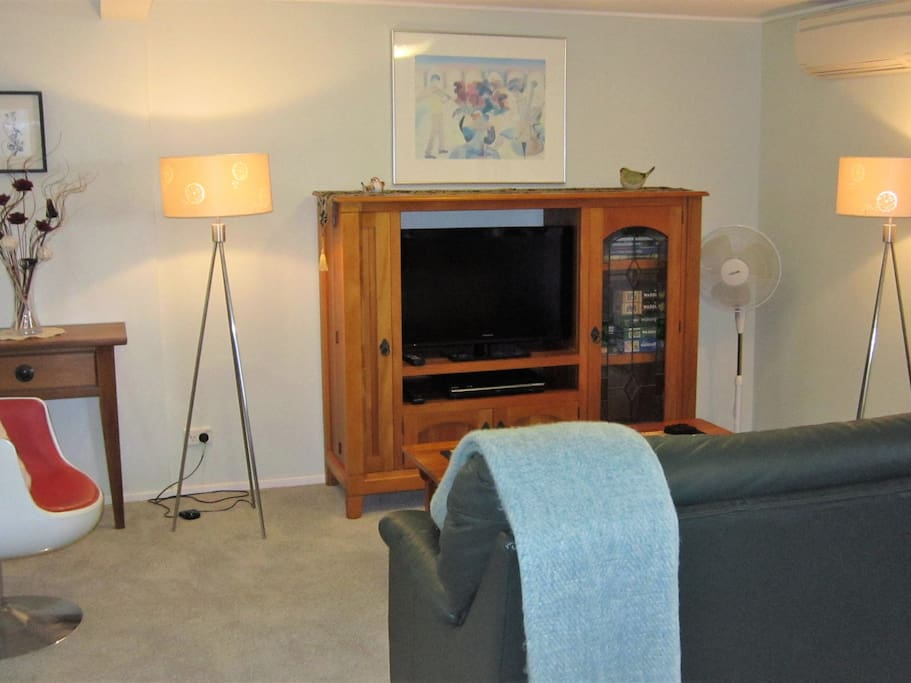 Living area. Ultra-fast wifi means your devices will stream movies easily. There are DVDs, books, puzzles and games in the TV cabinet and a wide range of tourist information in the hall table. There is a heat pump/AC unit and a movable pedestal fan.
