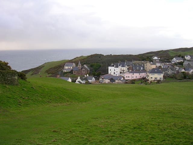 View of the house from the hills behind. Tall White House in the centre of the picture. To the right of the old chapel.