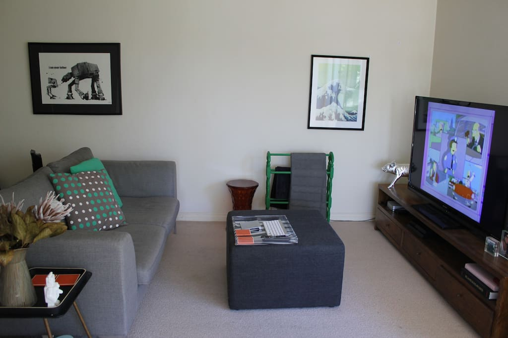 Open lounge room with comfy couch & large TV