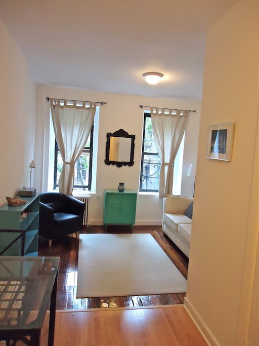 Uncluttered front room with hardwood floors, pretty street view