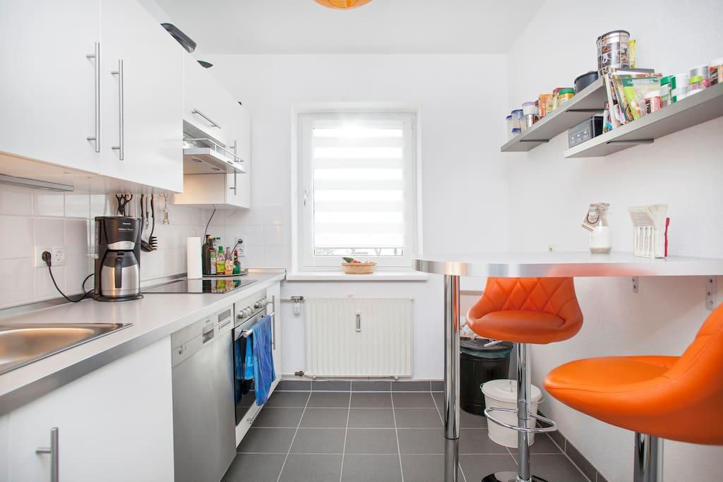 Küche mit Bartisch und zwei Barhockern.