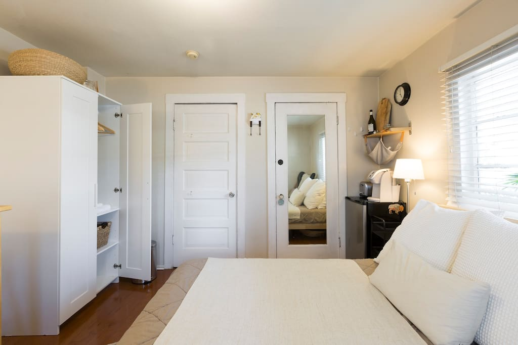 Queen size bed with small fridge, Kuerig, and toaster. Door w/ mirror goes outside, and other door goes to main house living room.