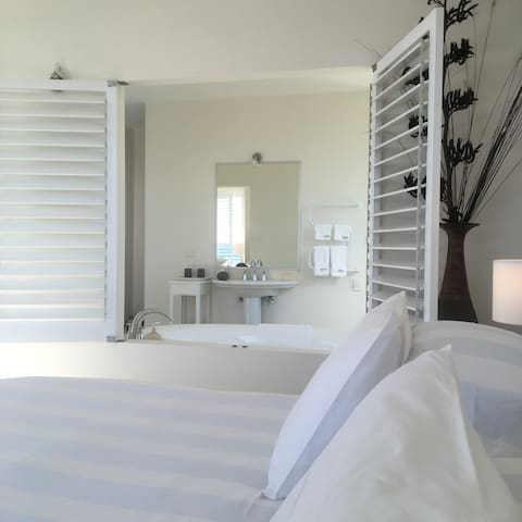View from openplan white bedroom to luxurious tiled bathroom