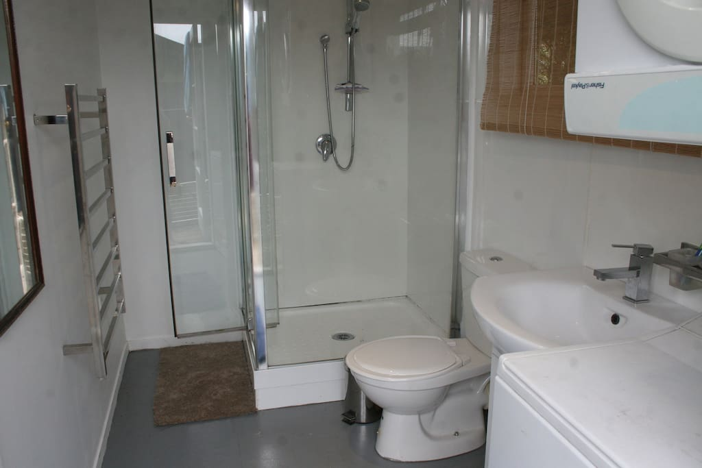 Modern bathroom with 2 entrances, as an ensuite to main bedroom, or accessible from large courtyard area. Has washer, dryer,heated towel rack, shower basin and toilet.