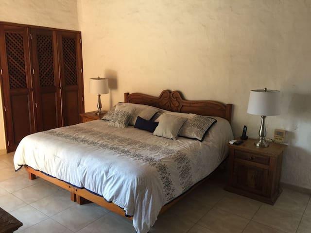 Recámara Principal con cama King Size, baño completo dentro de la habitación, AC y televisión (Planta Alta).