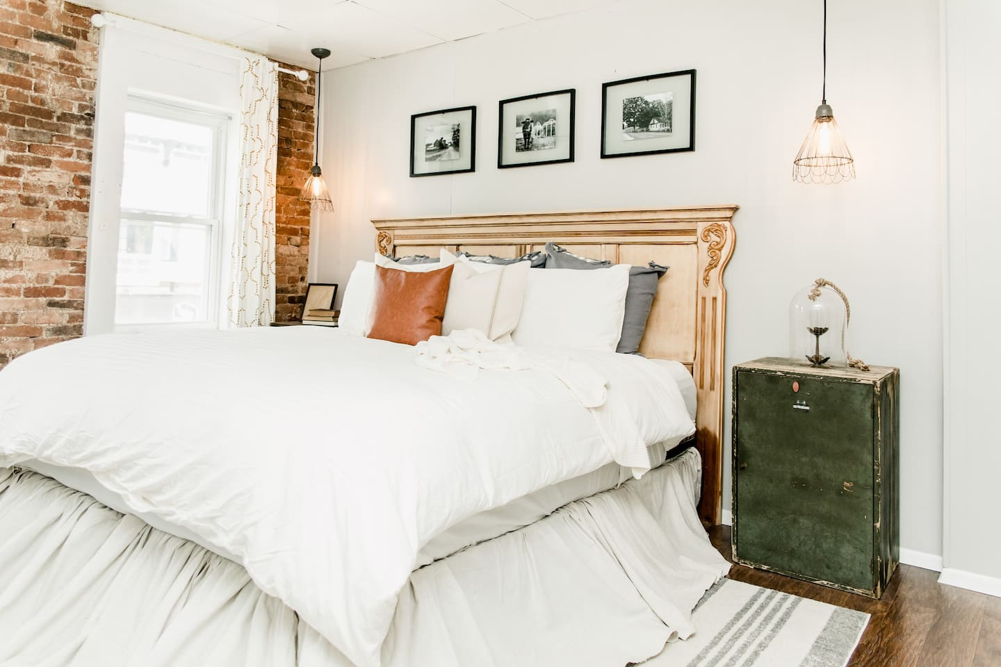 Master bedroom with an exposed brick wall. King size bed.