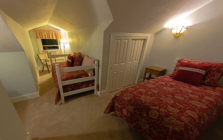 """Pass through the lounge geared for young children to """"The Flagstaff Room"""" furnished with a custom twin day bed and twin, antique dry sink and reading chair.  A room air conditioner insures you are cool in summer."""