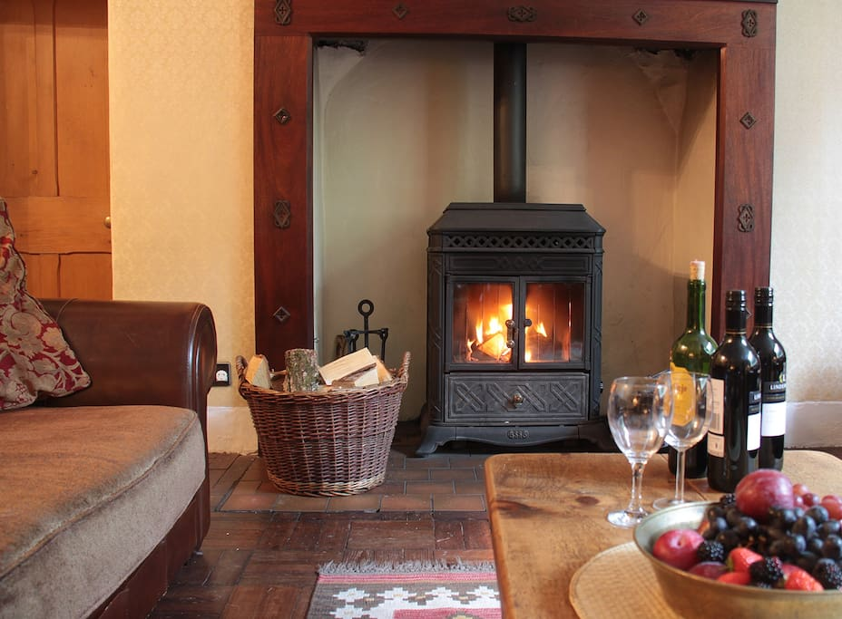 Cosy living room with wood-burning stove and Victorian inglenook fireplace.