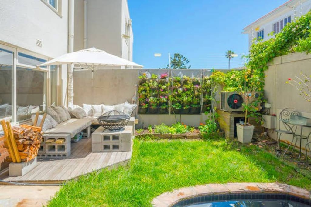 This is your private garden, with a small splash pool, nice seating areas, an herbal garden, a lime tree, granadilla, strawberries, blueberries, and an outside fire place.