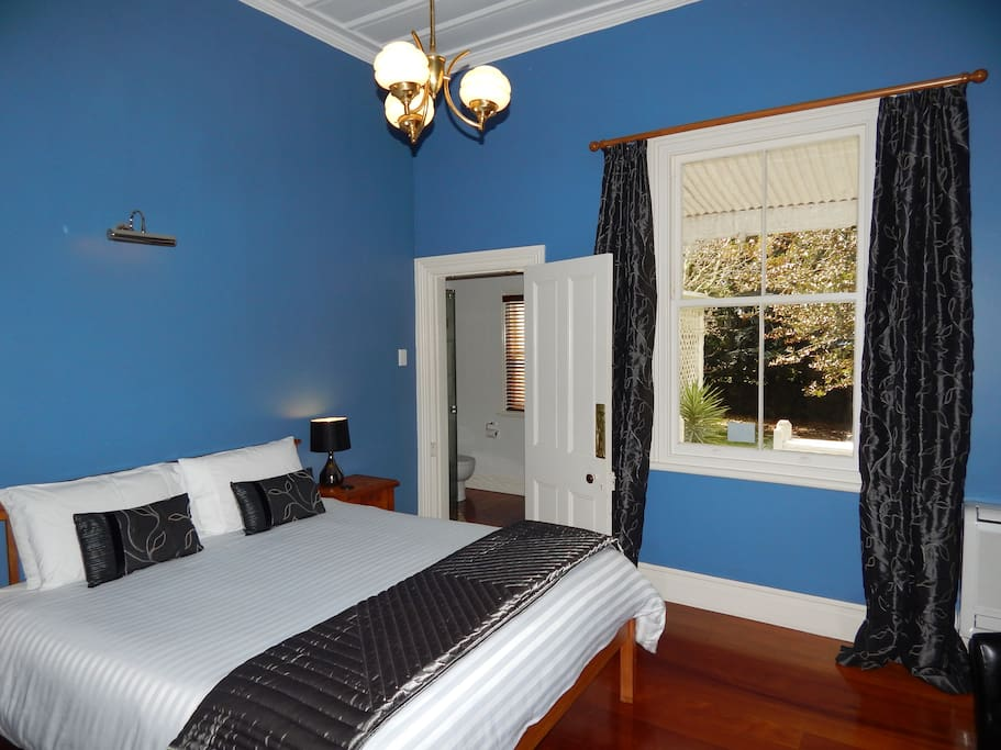 King-size bed in the main room with adjacent ensuite bathroom leading out to a private cerandah