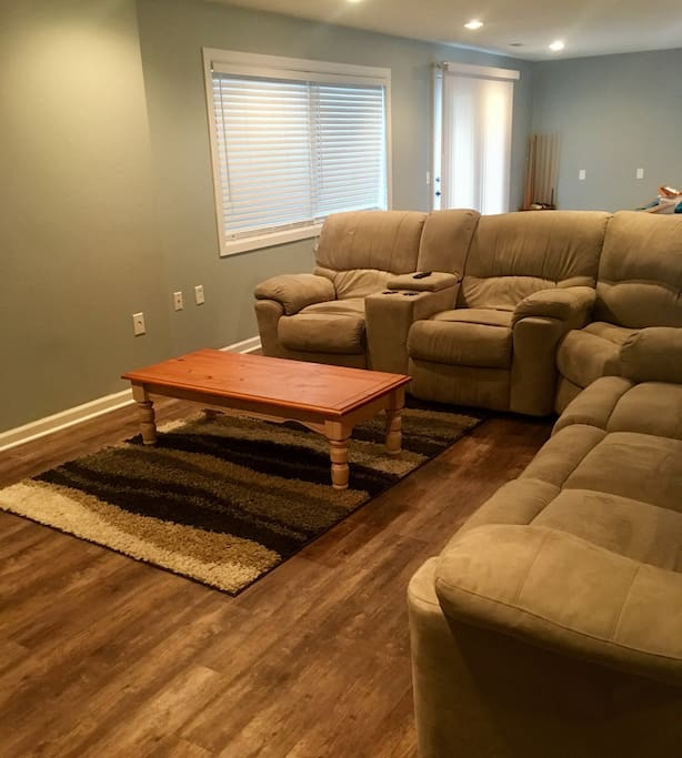 The basement complete with couch with recliners built in, a Smart TV, and PS4.
