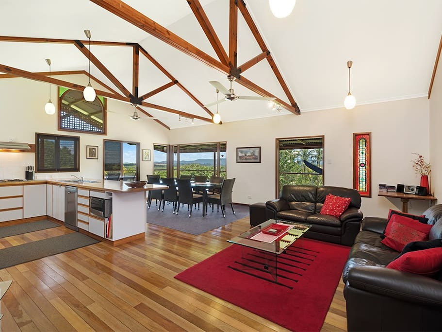 Open plan lounge and dining area with high ceilings.