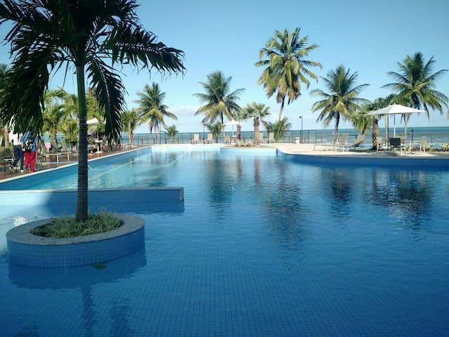Área de piscina com o mar mais a frente.