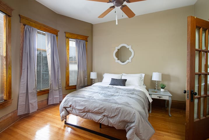 Bedroom 2 features a queen bed, 3 bay windows,  a large walk in closet and has access to the private patio overlooking Academy Street downtown Kalamazoo.