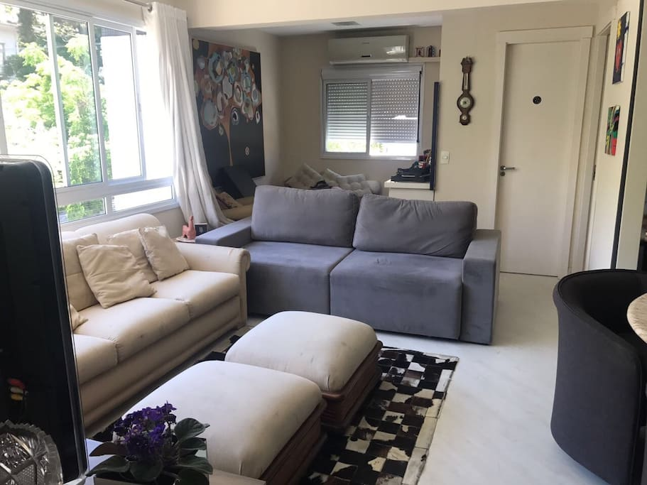 Sala com quarto integrado, sofás, televisão, TV a cabo, ar condicionado e mesa de mármore  com 4 lugares