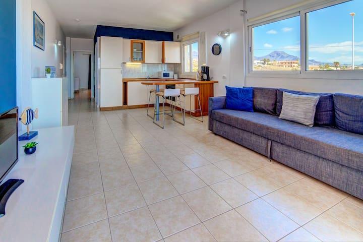 Living room and open kitchen with a view of the mountains / Salon et cuisine ouvert avec vue sur les montagnes / Salon y cocina abierta con vista a las montañas