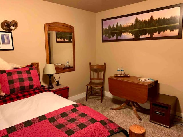 Teton room with queen bed has a warm wilderness feeling to it.  Mini fridge/freezer in the room with a table and chair. On-suite vanity with sink and closet.  Bathroom has large walk in shower with sink and toilet.