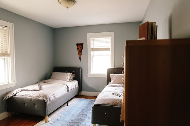 Cozy bedroom with 2 new Leesa mattresses on twin-sized beds —can be converted to 1 King-sized bed with foam mattress topper. Vintage Illini pennant; UIUC Library card catalog + Urbana High School Rosemary Yearbooks from 1950s.