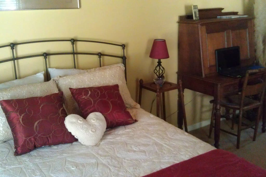 lovely guest bedroom with attached half bath and antique furnishings.