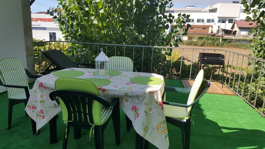 Varanda com cadeira longa, mesa com 4 cadeiras e grelhador