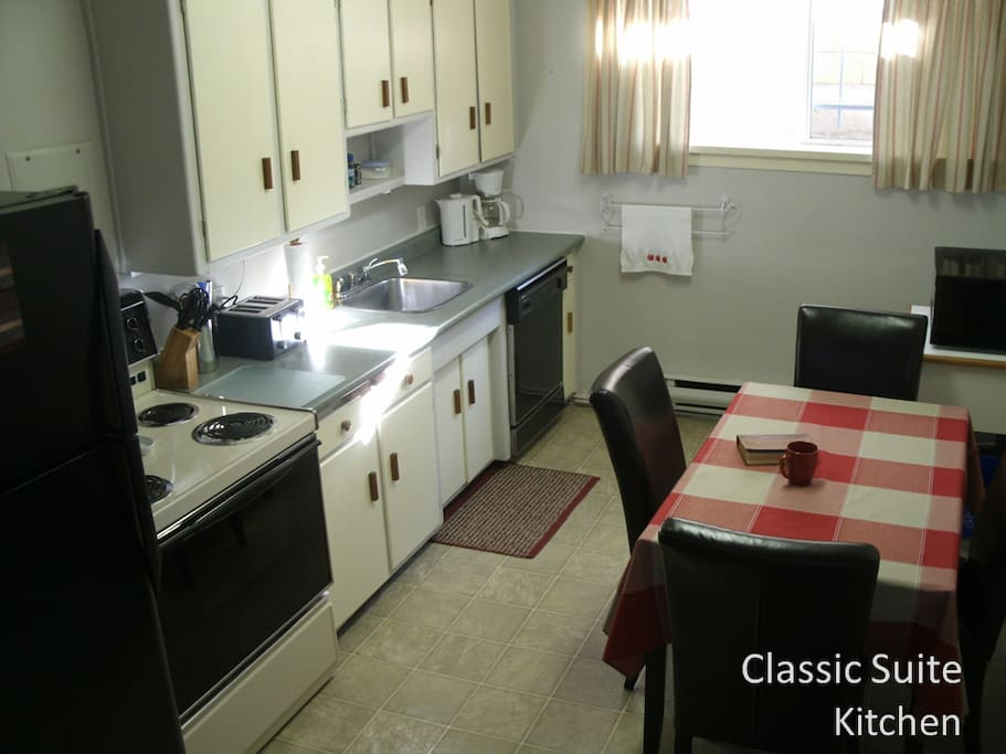 Fully equipped kitchen with dishes, cutlery, pots, pans, dishes, cutlery, pots, pans, oven, fridge, dishwasher, table with four chairs, microwave on stand, toaster, electric kettle, and coffee maker.