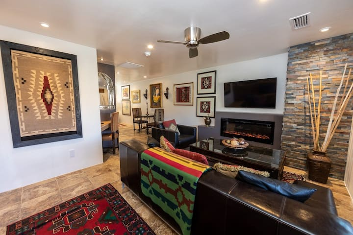 The living room area has a full kitchen, beautiful red rock views, electric fireplace, HDTV, large leather sofa and chair.