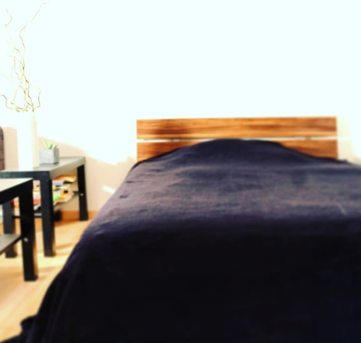 Das 1,40 m breite Bett mit vielen Büchern auf Deutsch, Spanisch und Englisch für die Gutenacht-Lektüre.