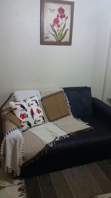 Sofá cama na sala, com ventilador de teto.