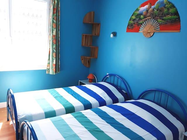 Une première chambre lumineuse avec deux lits 90*190 et un volet roulant électrique.