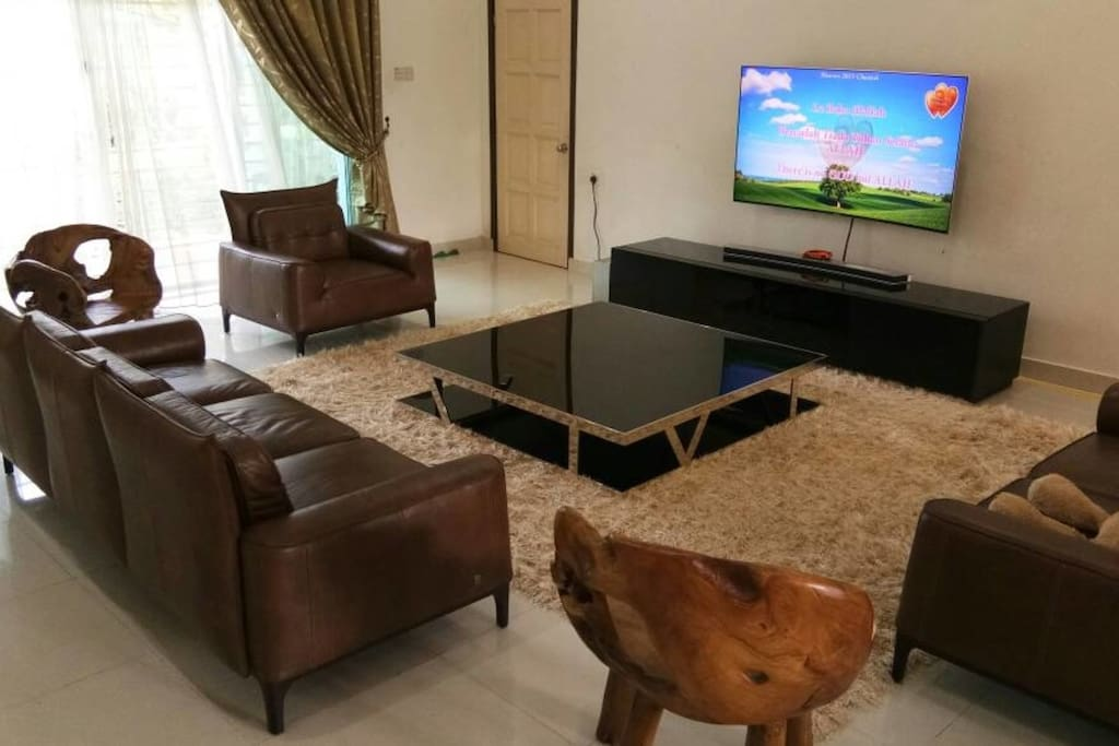 Large living room with 65 inches smart SAMSUNG TV and 8 seaters genuine leather sofa.